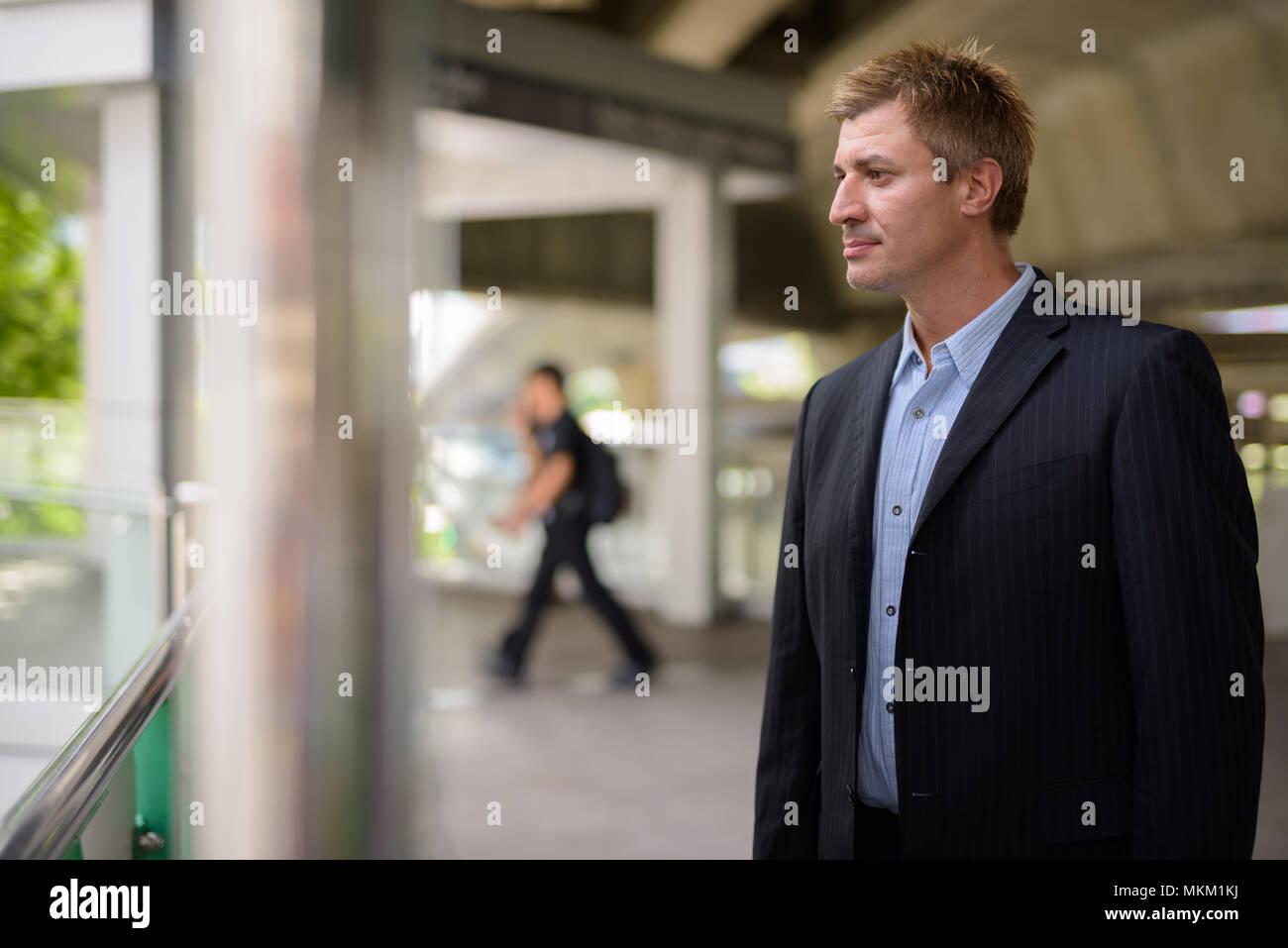 Businessman at the sky train station in Bangkok, Thailand - Stock Image