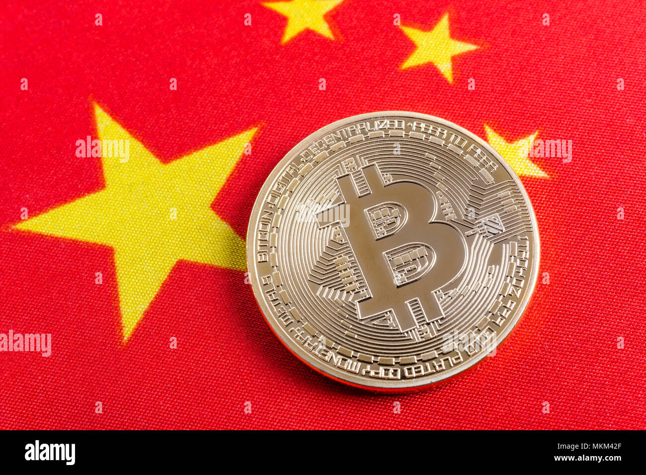 Bitcoin real coin over chinese flag fabric - Stock Image