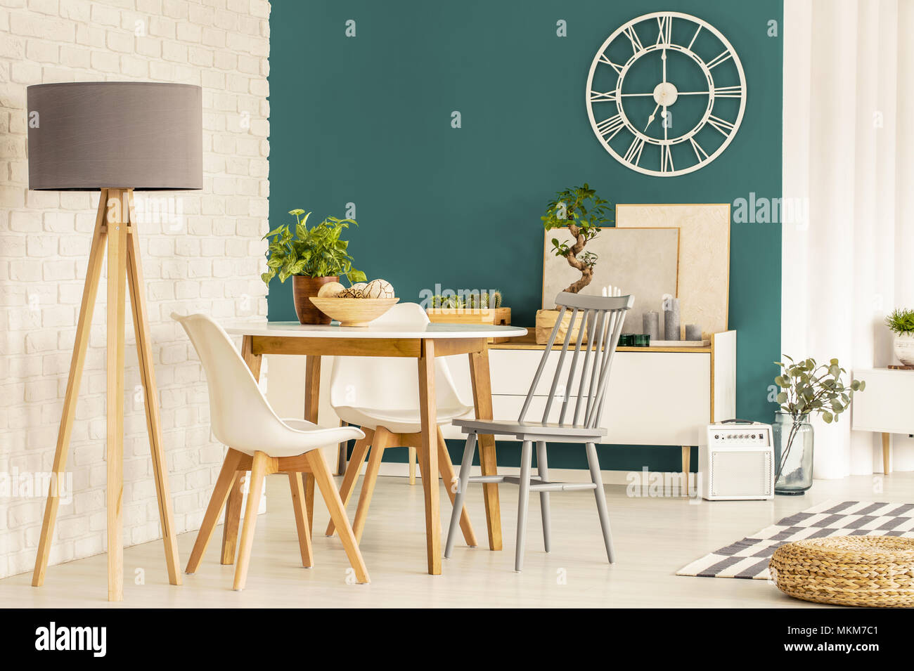 Grey lamp next to chairs at wooden table in green dining room interior with gold round clock - Stock Image