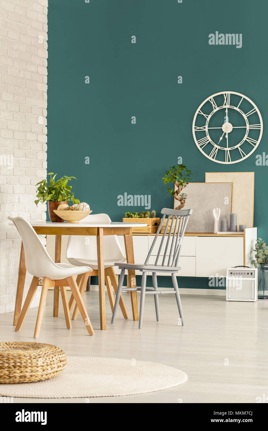 Pouf next to chairs at wooden table in green dining room interior with round gold clock - Stock Image