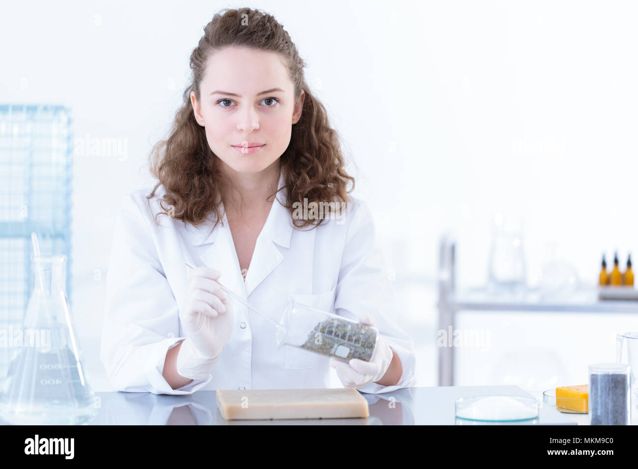 Portrait of a chemist in white uniform getting a sample of a substance from a beaker - Stock Image