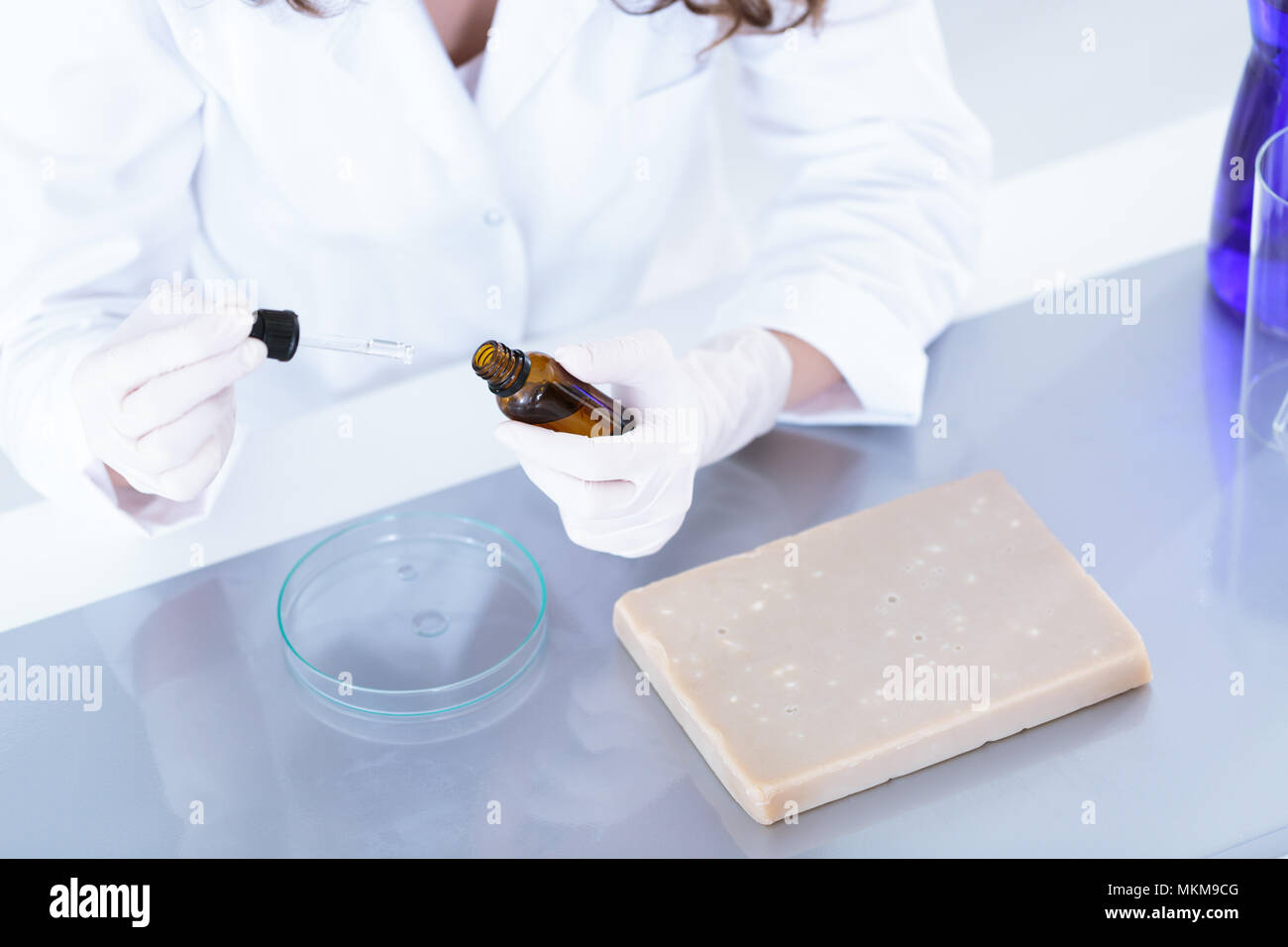 High angle of laboratory worker preparing a sample of a liquid for examination - Stock Image
