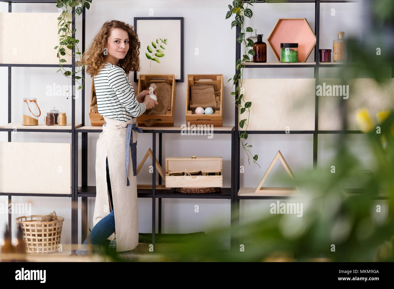 Smiling saleswoman arranging natural healthcare products on wooden boxes in the shop Stock Photo