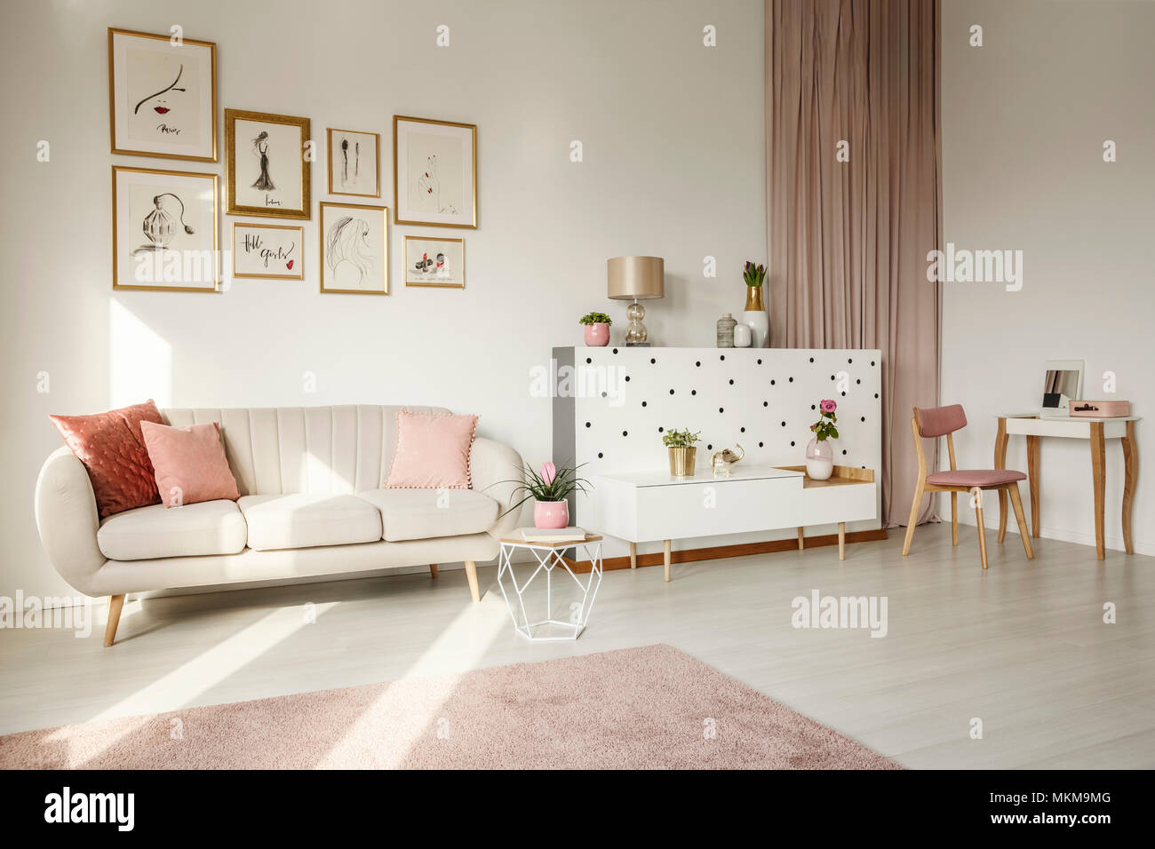 Pink flower on table near sofa in feminine living room interior with ...