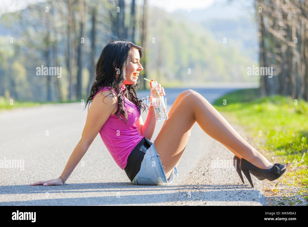 18 years teen girl sitting on empty country-road happy smiling away stiletto big heels alpfabet - Stock Image
