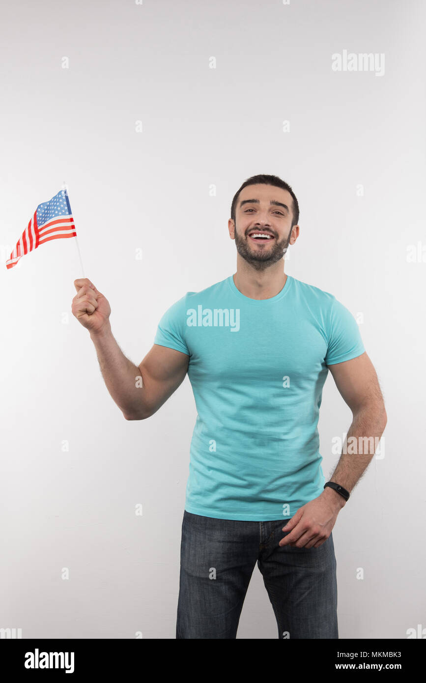 Delighted nice man holding a US flag - Stock Image