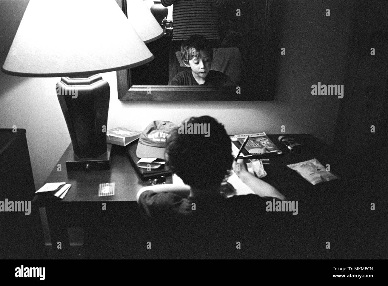 Six year old boy writing postcards in a hotel room, Hotel Pennsylvania  New York City, United States of America. - Stock Image