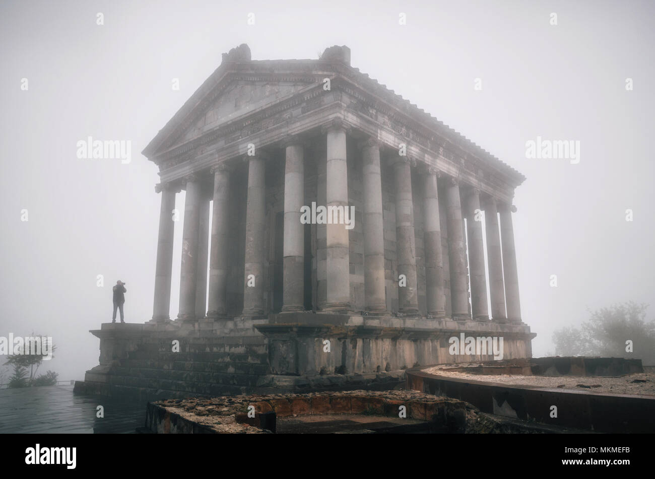 Garni hellenistic pagan Temple with silhouette of tourist taking photo in fog, Republic of Armenia - Stock Image