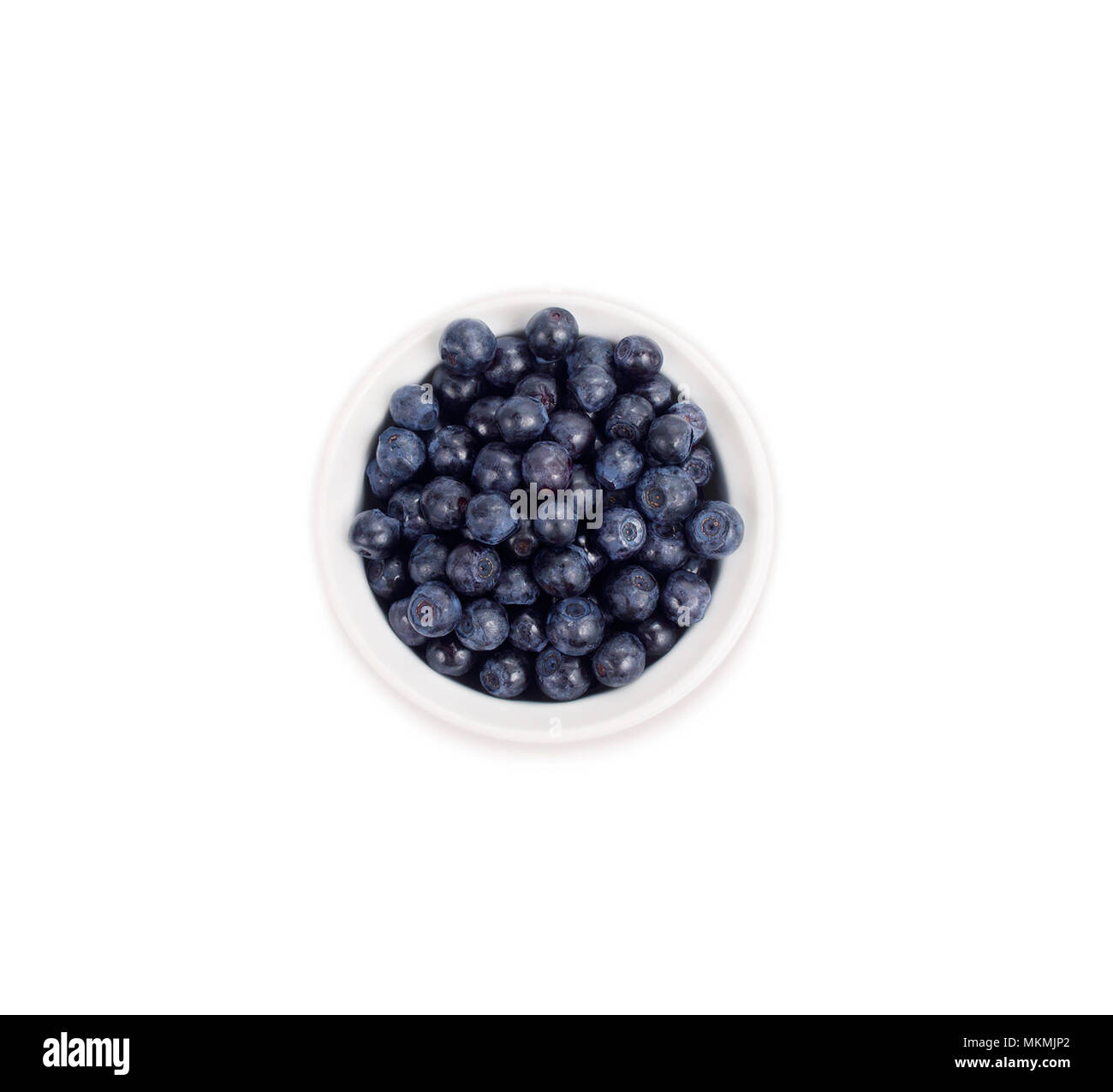Bilberries in a wooden boin a white ceramic bowl. Top view. Ripe and tasty blueberries isolated on white background. Stock Photo