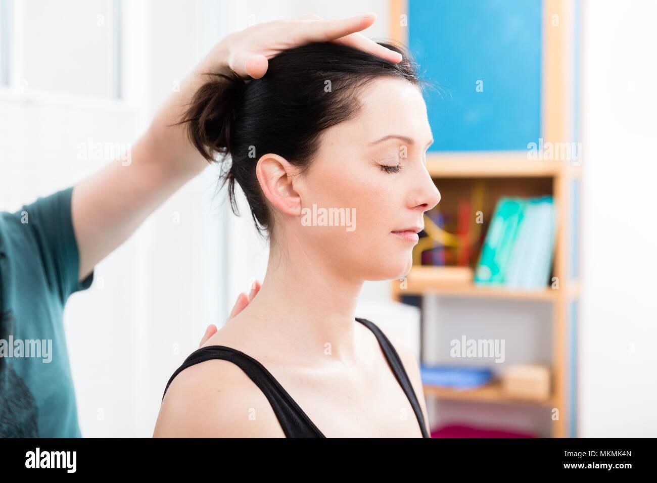 Woman having head massage from physiotherapist - Stock Image