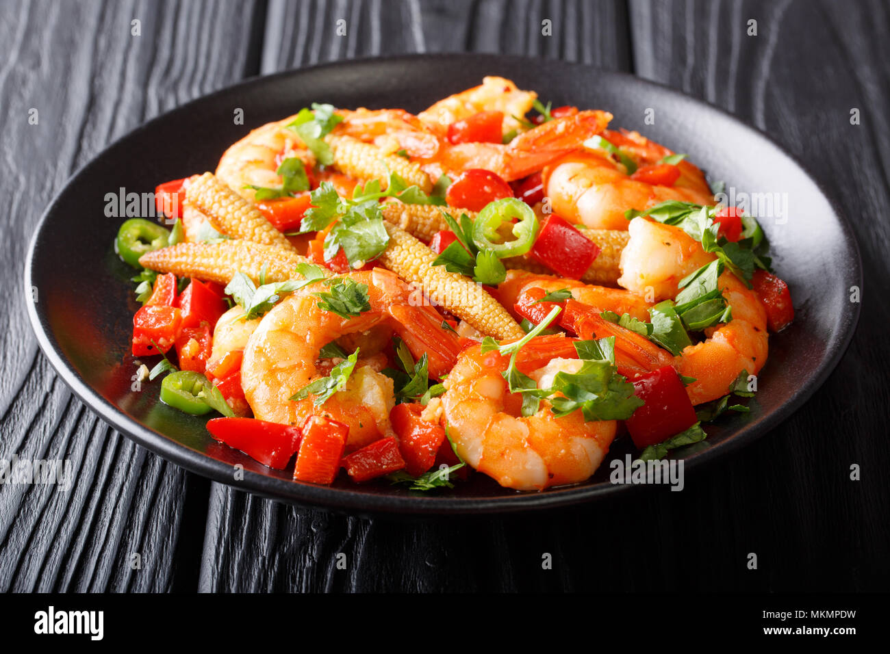 Freshly prepared Mexican prawns with sweet peppers, chili, garlic, corn cobs and herbs close-up on a plate. horizontal - Stock Image