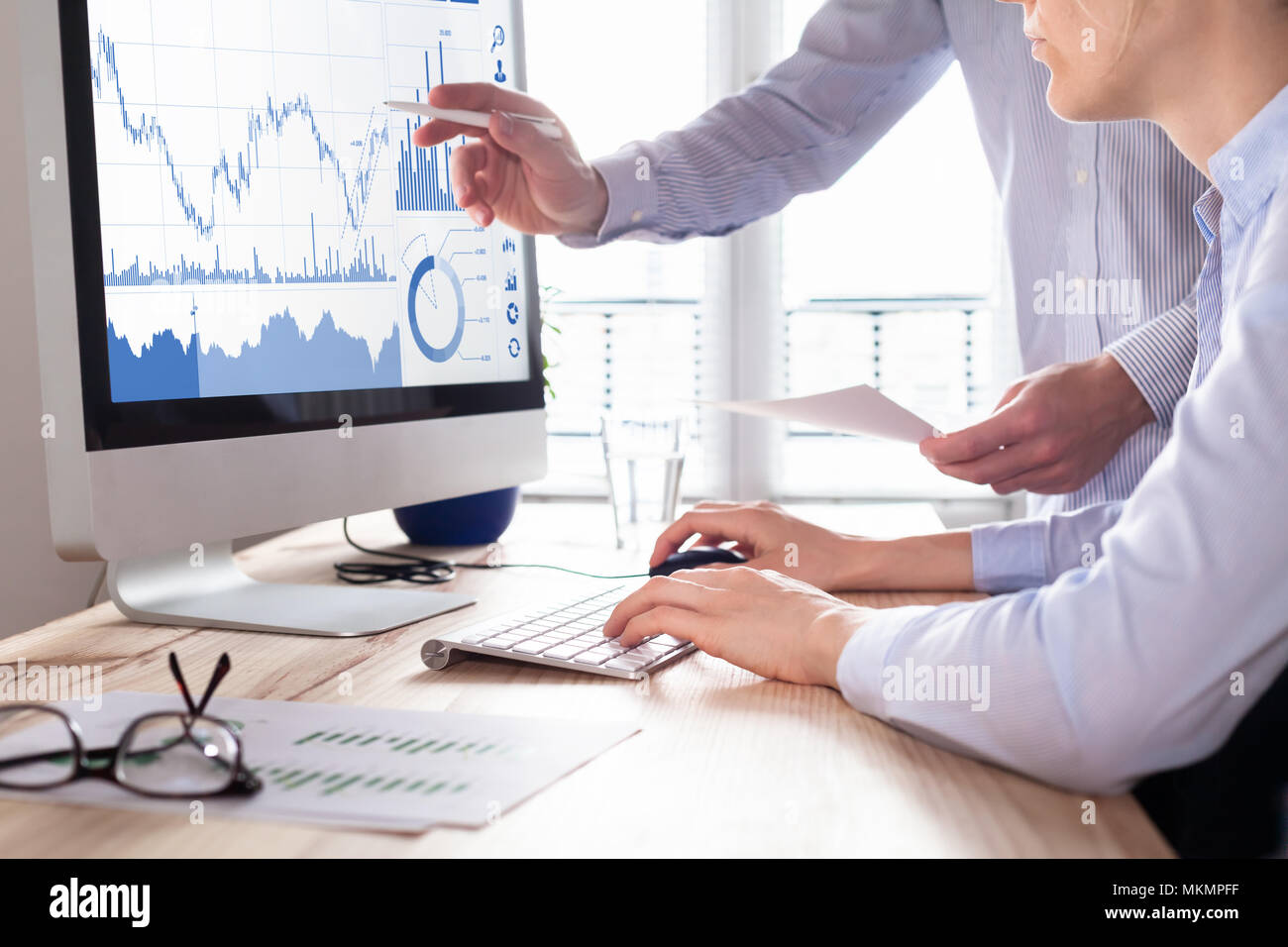 Traders discussing trading strategy for better profit and return on investment (ROI) by analyzing stock market and foreign exchange (forex) charts on  - Stock Image