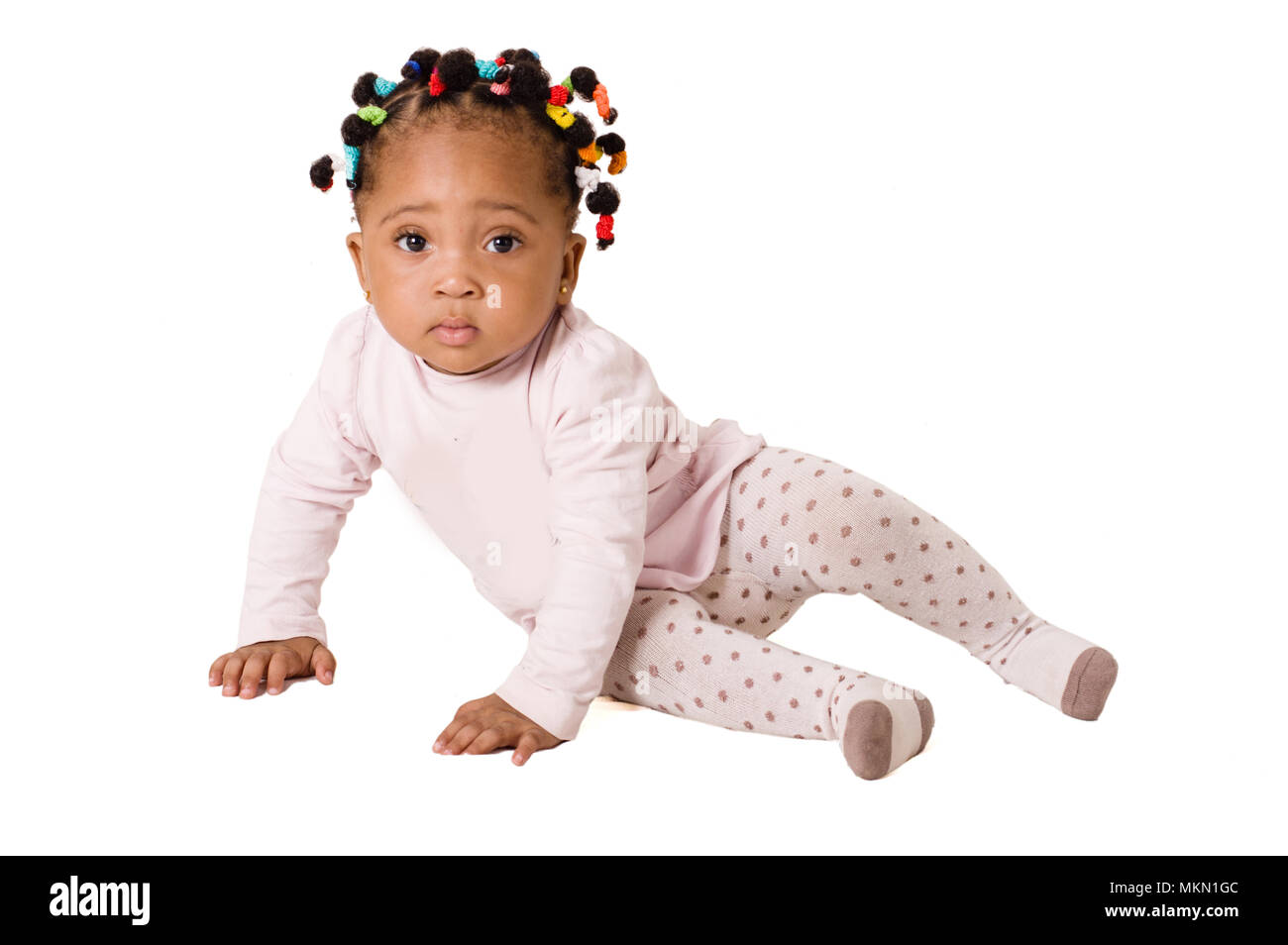 Portrait of nice baby sitting and looking at the camera on a white background - Stock Image