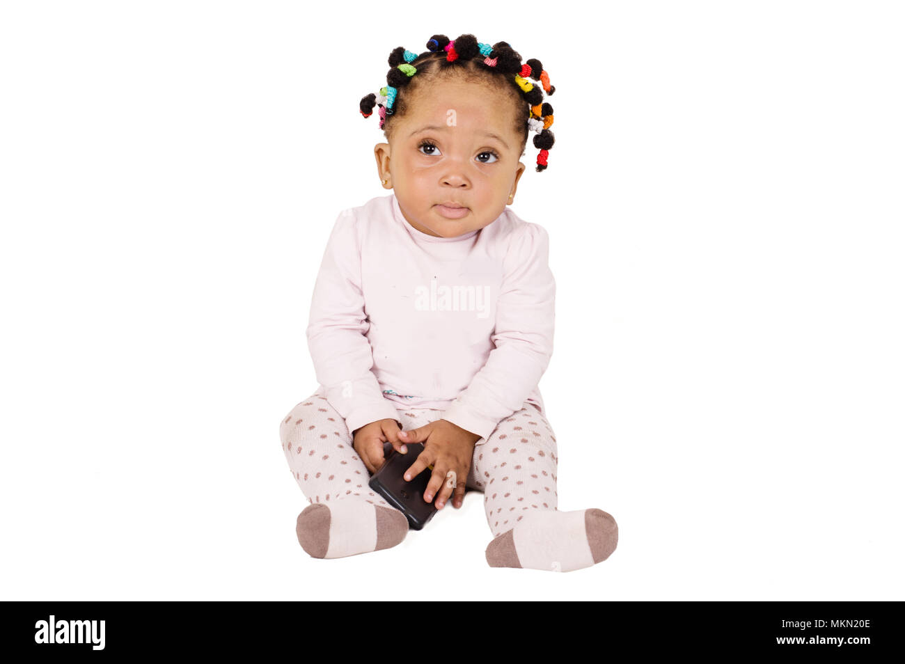 Pretty baby sitting and playing with a cell phone on white background - Stock Image