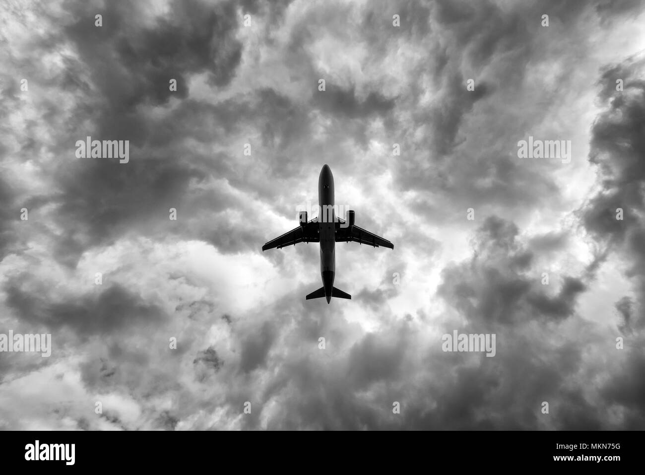 under a big jet plane taking off, black and white - Stock Image