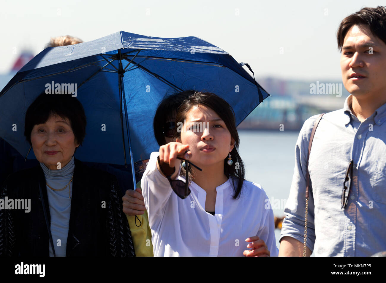 Woman appears to be pointing to the camera objecting to be photographed but is really pointing out a landmark to her family or friends. - Stock Image