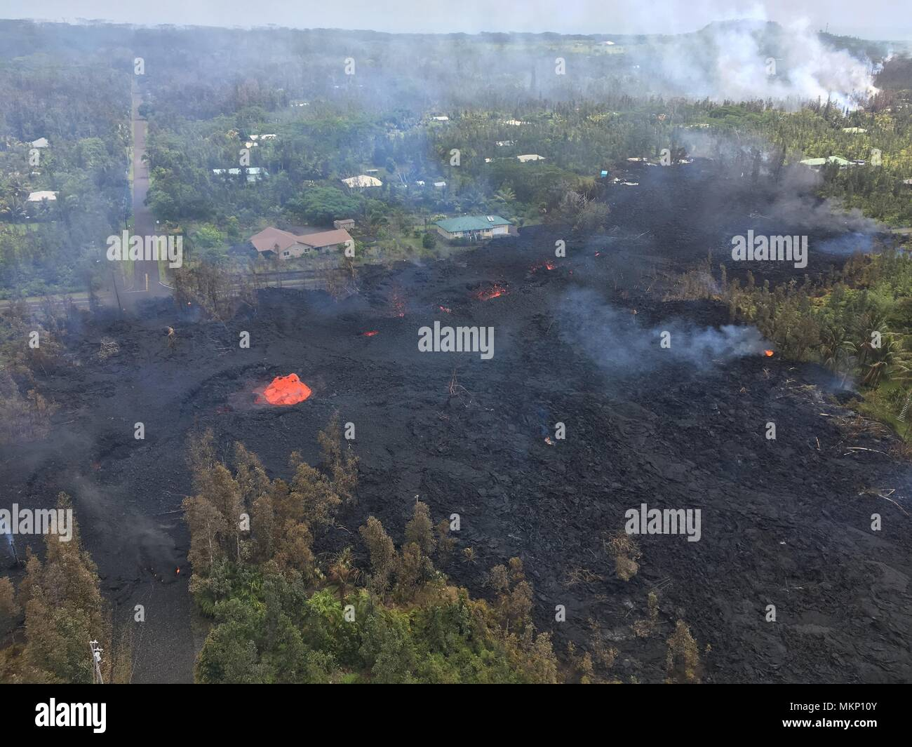 A pyroclastic lava flow from the Kilauea volcanic eruption moving toward a subdivision along Hookapu Street May 5, 2018 in Leilani Estates, Hawaii. The recent eruption continues destroying homes, forcing evacuations and spewing lava and poison gas on the Big Island of Hawaii. - Stock Image