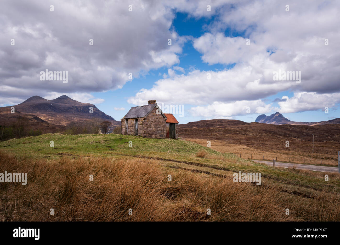 Derelict farm house byre or croft building in remote landscape of North West Highlands of Scotland. Mountains L to R Cul Mor and Suilven - Stock Image