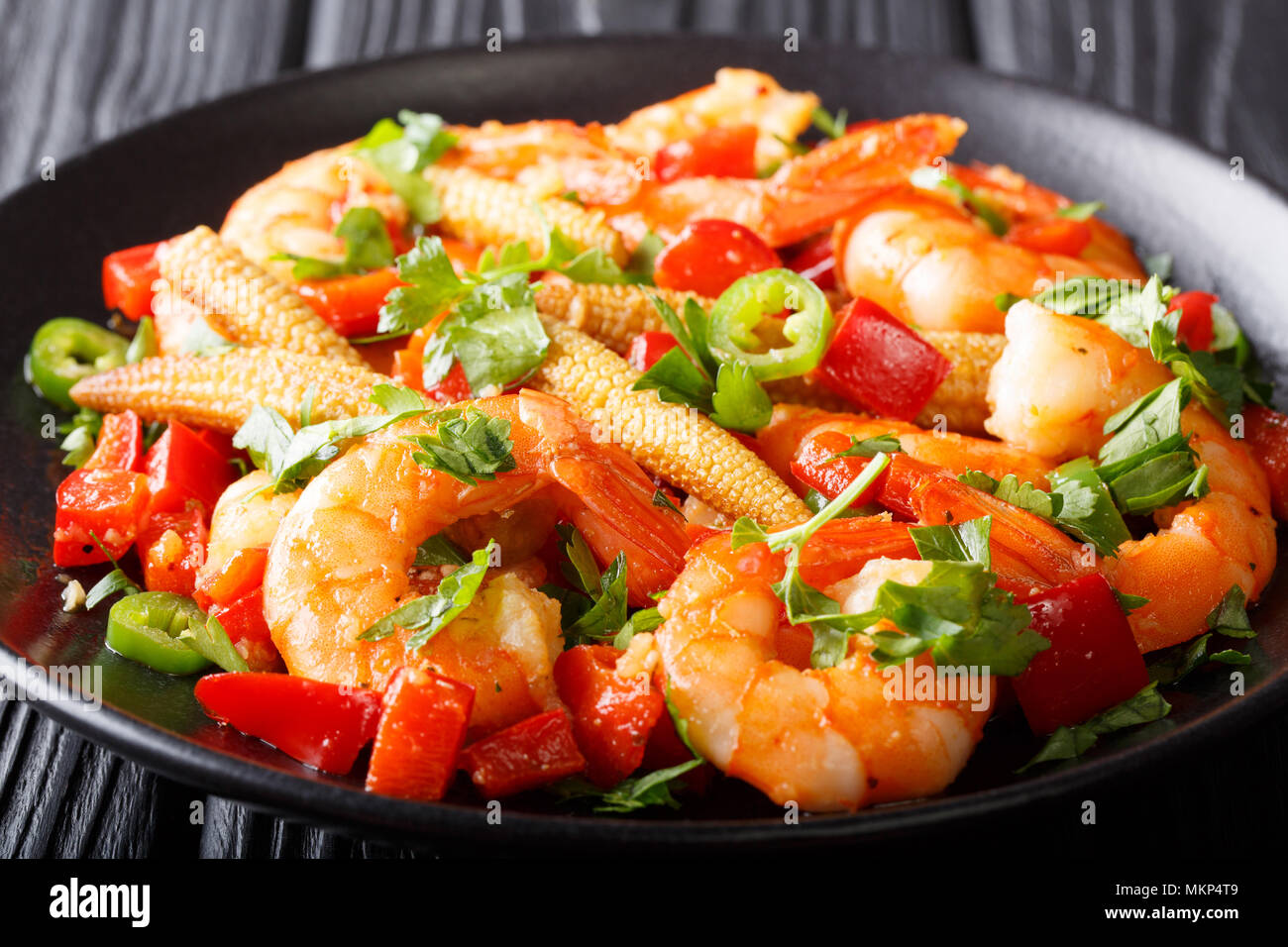 Mexican delicious prawns with pepper, garlic, corn cob and herbs close-up on a plate. horizontal - Stock Image