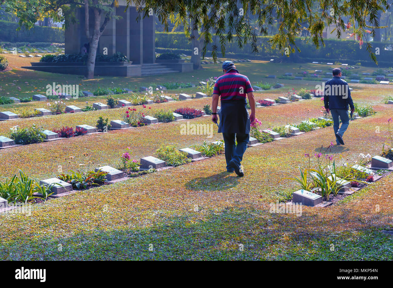 Visitors at the WWII cemetery in Guwahati, India. The war cemetery was set up during WWII for burial of servicemen killed in the war. - Stock Image