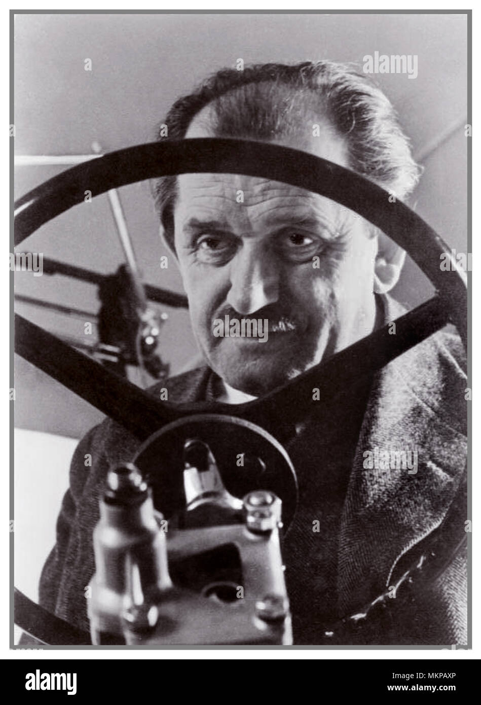 1940 Dr Ferdinand Porsche, environmental portrait viewed through his 'people's car' steering wheel (his invention and creation) a KDF-Wagen VW Beetle Volkswagen Adolf Hitlers vision of Strength Through Joy... - Stock Image