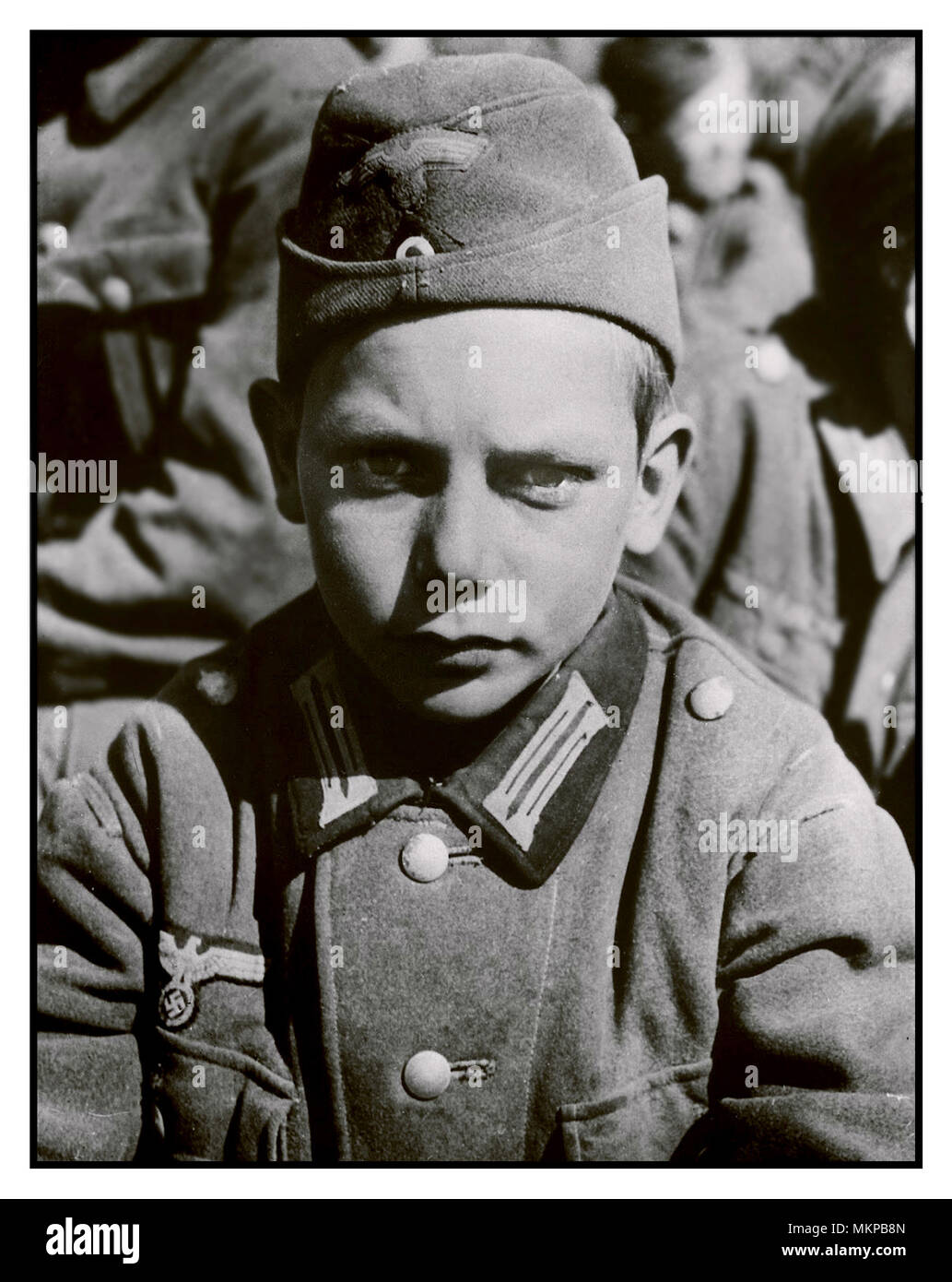 1945 WW2 Vintage Image 13-year-old POW from a Hitler Youth unit captured by the US Army in Martinszell-Waltenhofen, May 1945. Jugend troops with boys as young as 12 were widely used in the battle of Berlin as cannon fodder to buy a few hours to Nazi criminals busily fleeing to Switzerland, Argentina, Chile and Uruguay. The boys were dying in the last days and hours of war as obedient, loyal pawns when the fate of the Nazi state was sealed, - Stock Image