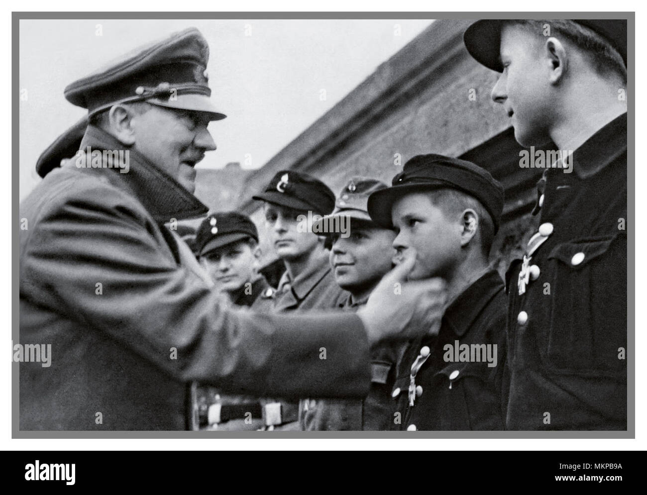 1945 Vintage German WW2 Propaganda Image Nazi leader Adolf Hitler  making probably last public appearance outside his Berlin Bunker meeting and awarding medals to loyal totally misguided Hitler Youth members.  Boys used callously as cannon fodder against Russian encirclement April 1945 WW2 - Stock Image