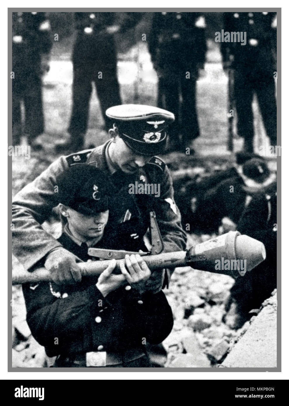PANZERFAUST WW2 The German defense of Berlin. A German non-commissioned officer teaches a member of Hitler Youth the skills of firing a Panzerfaust, grenade launcher.They were the elite core of young troops under command of General Walter Wenck. At dawn on 28 April, the youth divisions Clausewitz, Scharnhorst and Theodor Körner were the vanguard of XII Army's offensive from south-west, attempting to break through the Soviet encirclement.They were made up of recent Hitler Youth, now young men from officer training schools, making them the best units,but outnumbered & catastrophically defeated.. - Stock Image