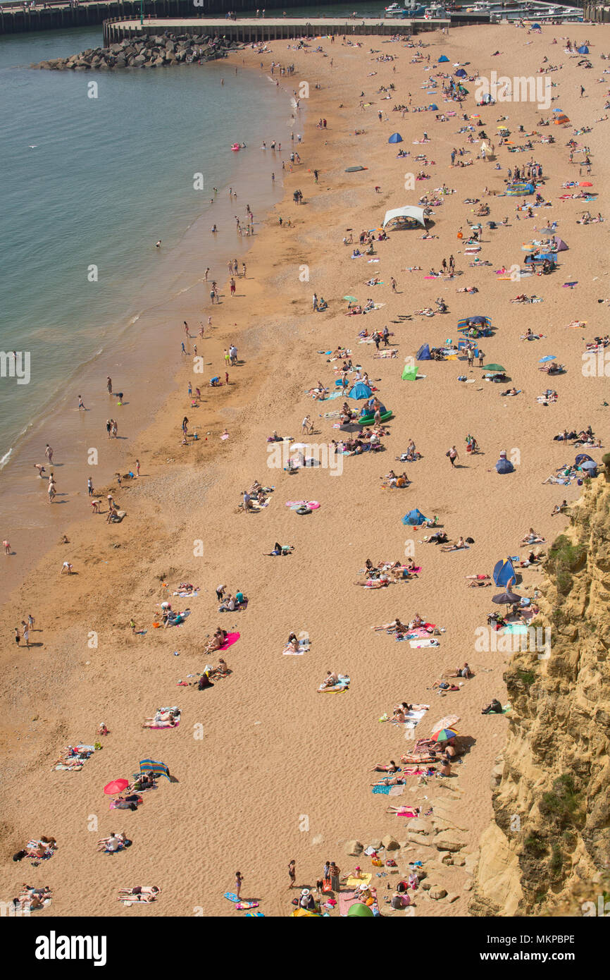 Visitors to East Cliff beach adjacent to West Bay and its harbour sunbathing and swimming. Viewed from the top of East Cliff looking westwards on the  - Stock Image