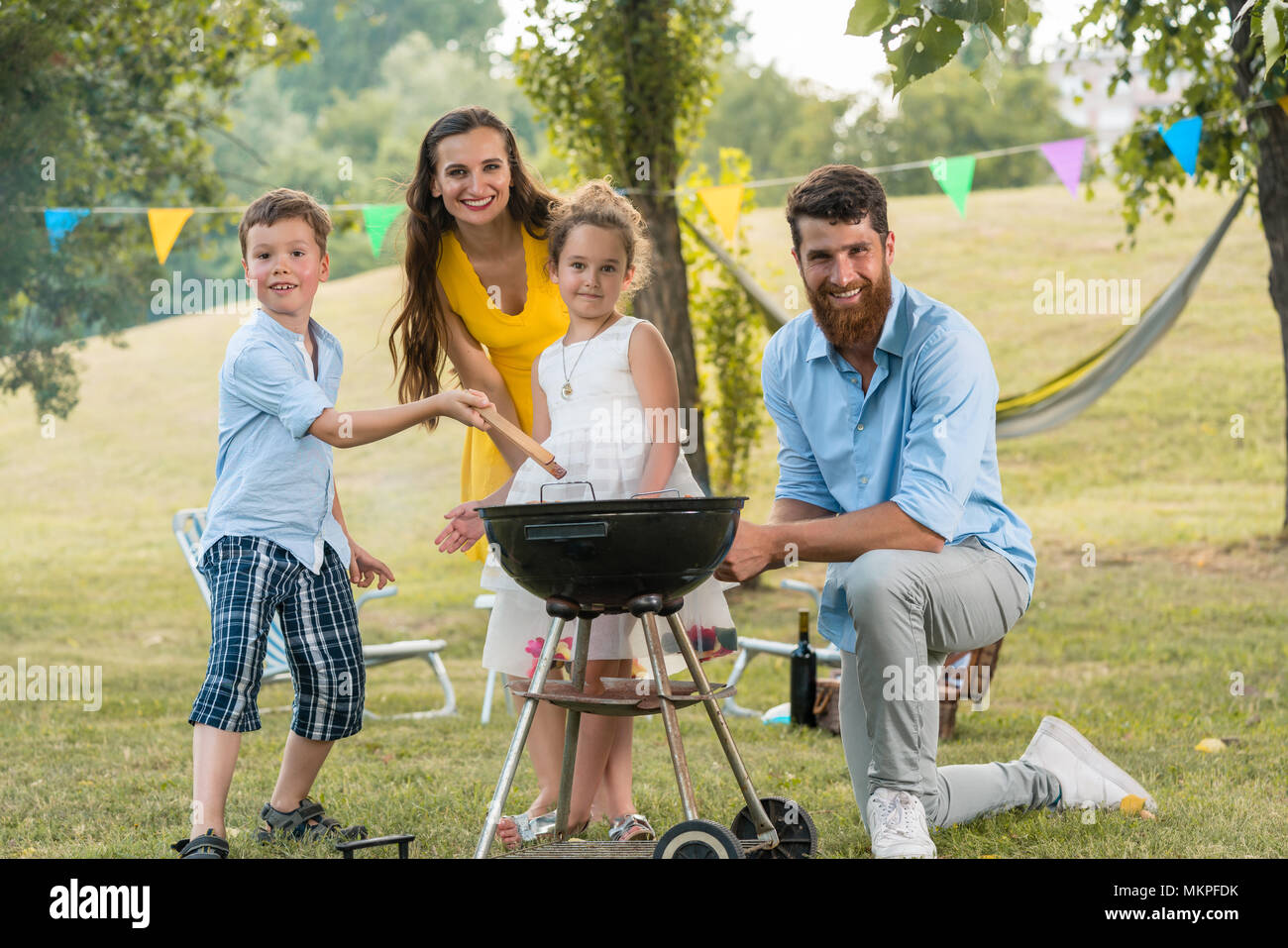 Portrait of happy family with children posing behind a barbecue  - Stock Image