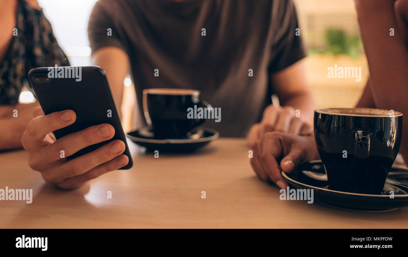 Close up of a smartphone being used by a man sitting at a cafe table with his friends. Young people having coffee and using mobile phone at coffee sho - Stock Image