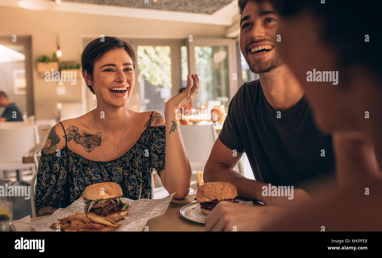 Cheerful young woman talking with her friends at restaurant with burgers on table. Friends hanging out at a cafe. Stock Photo