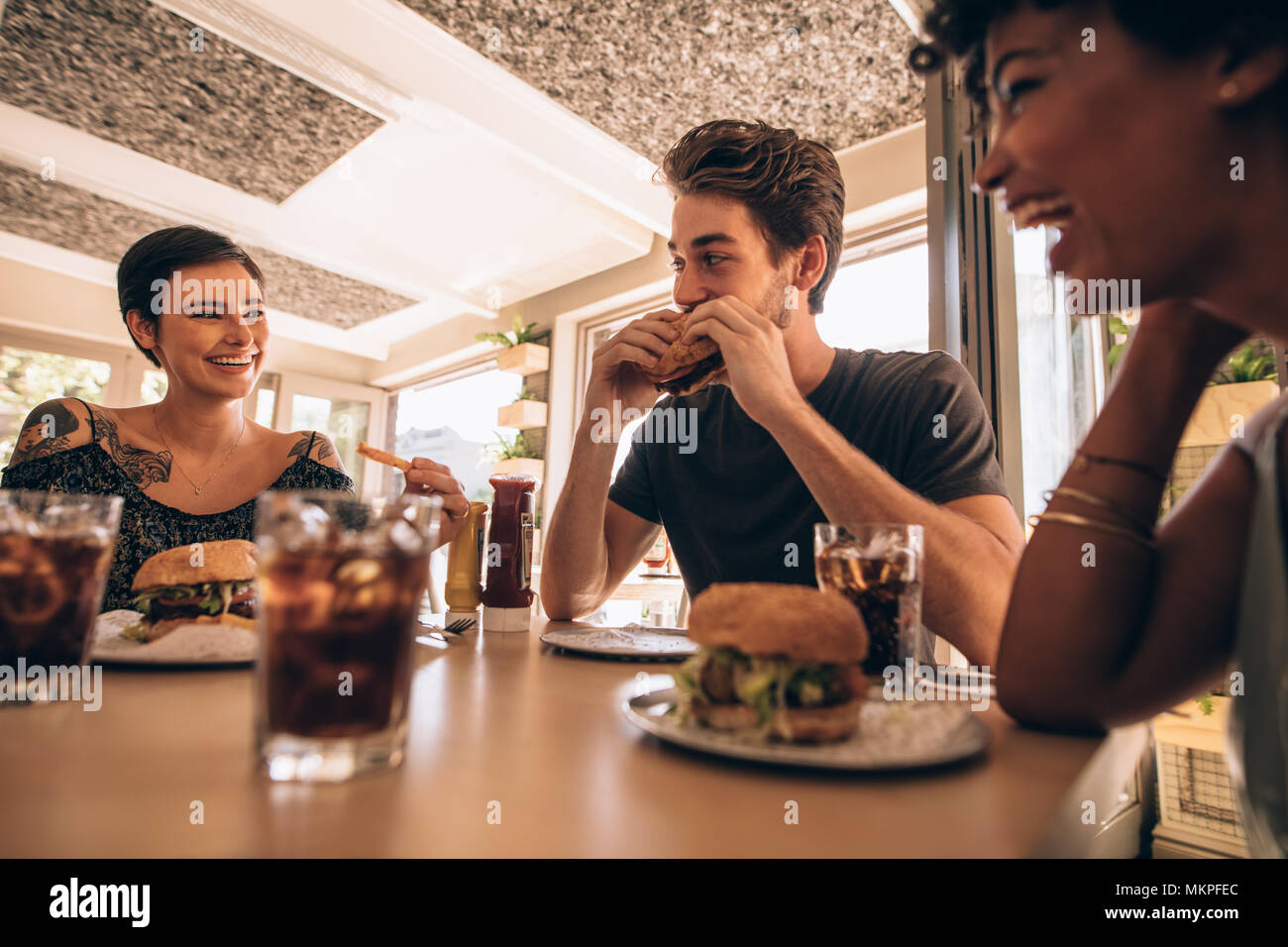 Group of friends meeting at a fast food restaurant. Man and women talking and having stack burger at a restaurant. - Stock Image