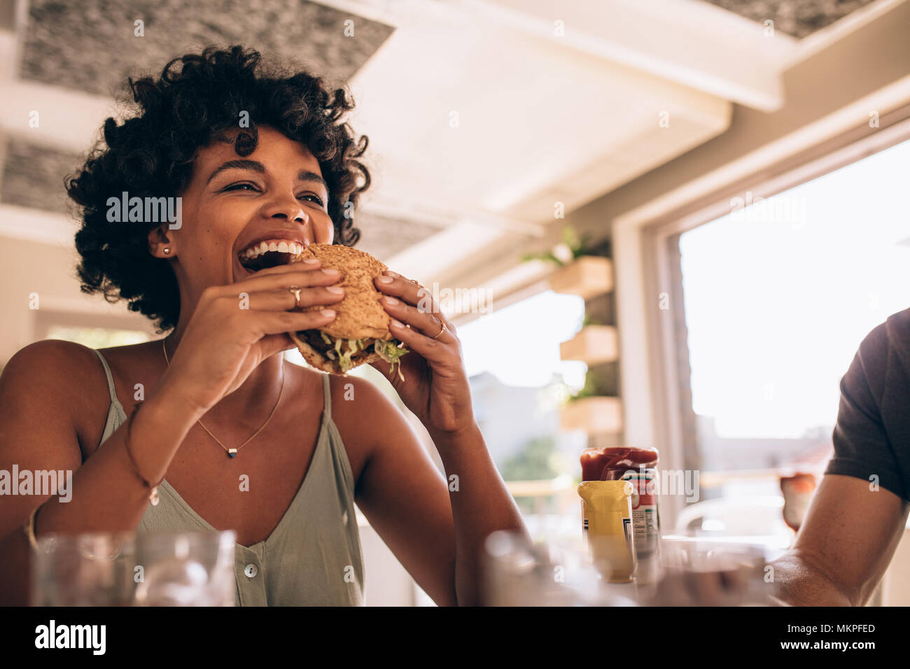 African woman eating stack burger at restaurant with friends. Happy young woman having junk food at cafe with friends. - Stock Image