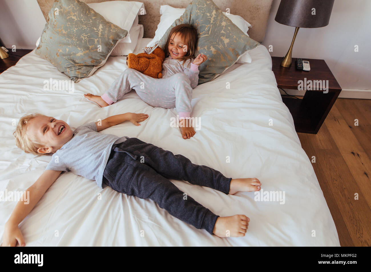 Little boy lying on bed with her sister sitting by holding a teddy bear smiling. Joyful little children playing in bedroom. - Stock Image