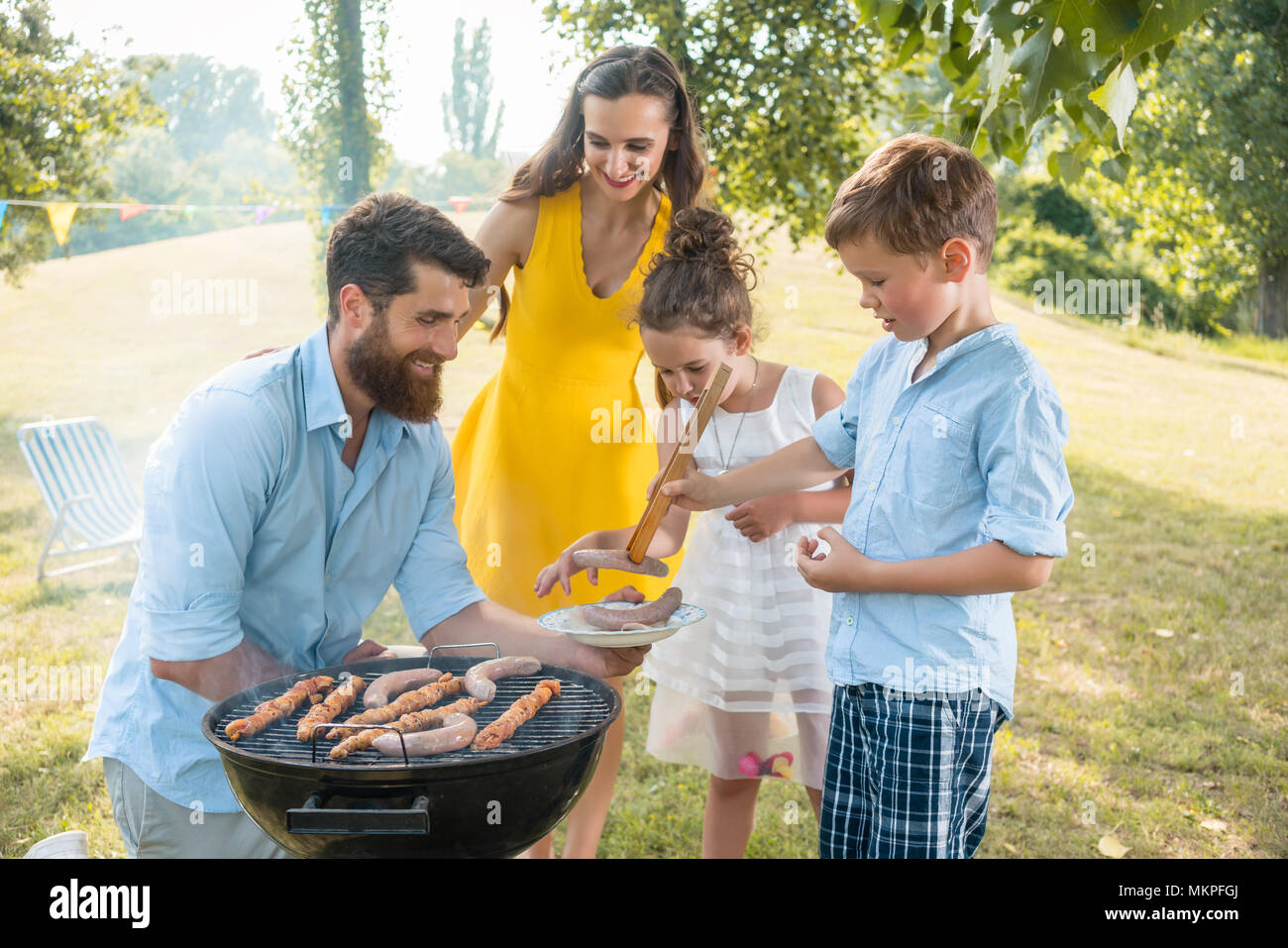 Dedicated father helping son to use wooden tongs during family picnic - Stock Image