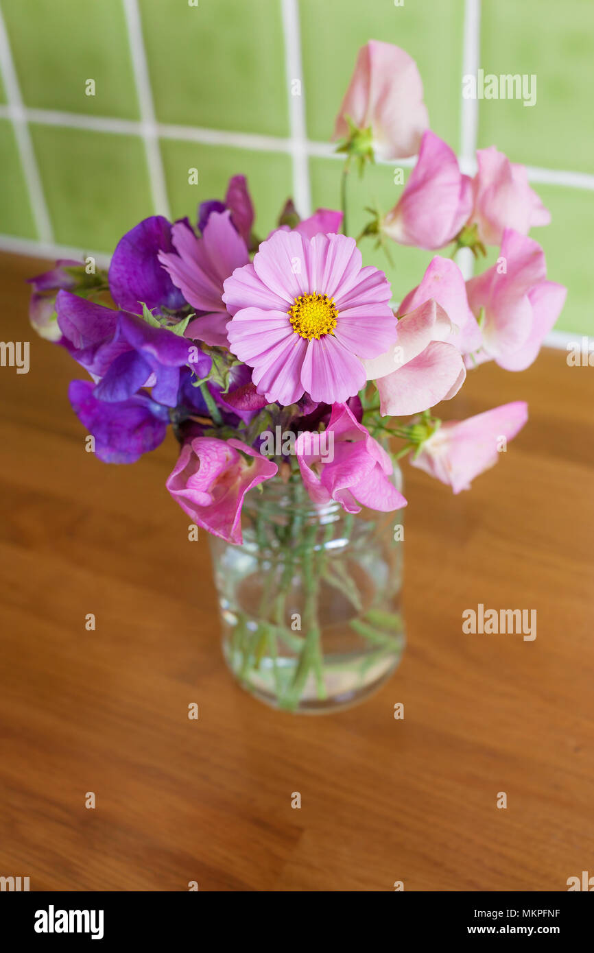 Mixed, fresh bunch of garden flowers in a jar on a kitchen table. Narrow depth of field with focus on Cosmos flower. - Stock Image