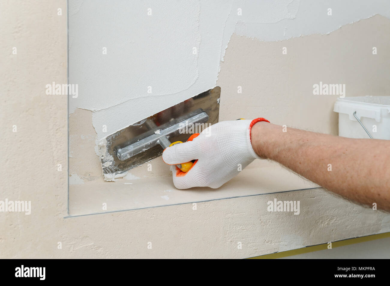 Decorative plaster coating  Man puts plaster on the wall