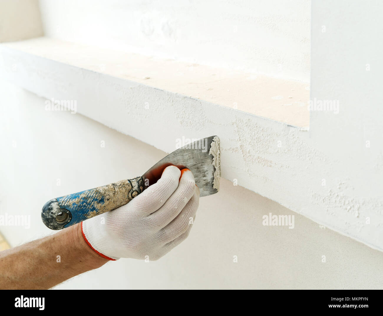 Decorative plaster coating  Man does ragged texture on the wall