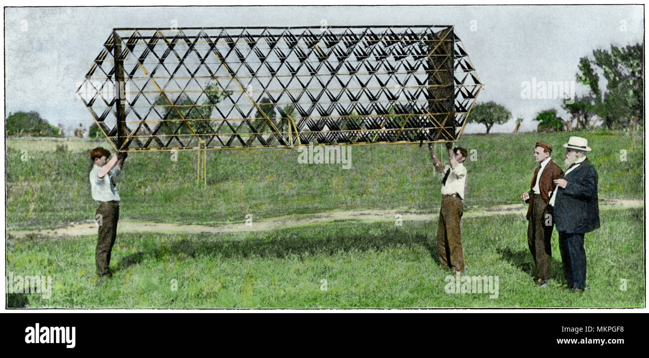 Alexander Graham Bell (right) experimenting with an x-beam tetrahedral kite with designer Mr. Baldwin, early 1900s. Hand-colored halftone of a photo - Stock Image