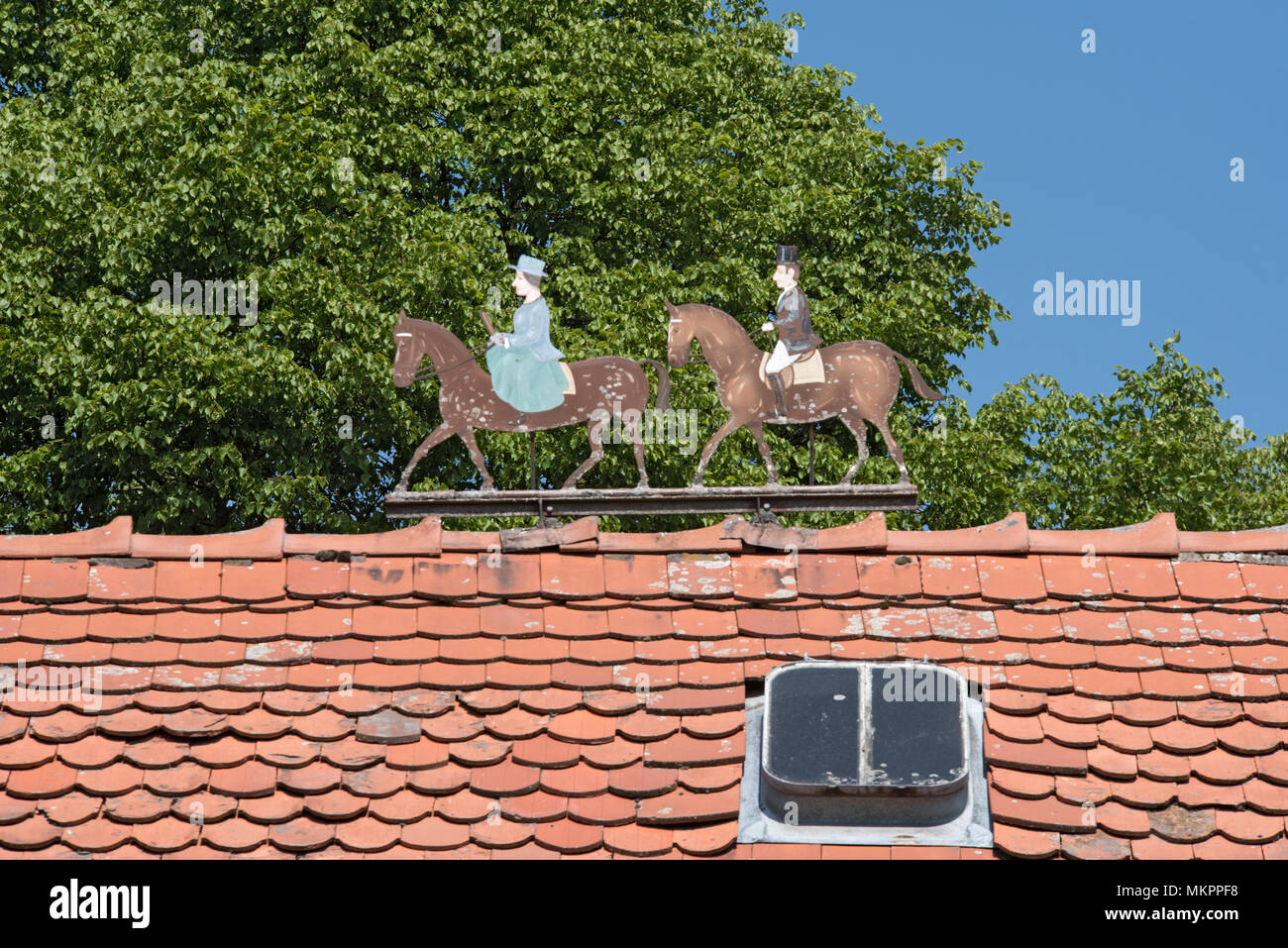 Metal figures two riders, man and woman on the roof of a estate - Stock Image