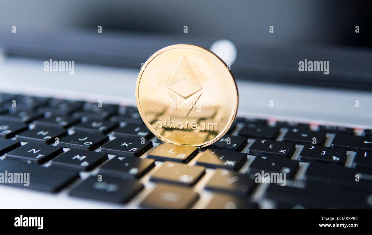 Gold Ethereum coin on a laptop. Ethereum crypto currency on a laptop black keyboard. Digital money and virtual cryptocurrency concept. Investment. Bussiness, commercial. Profit from mining. - Stock Image