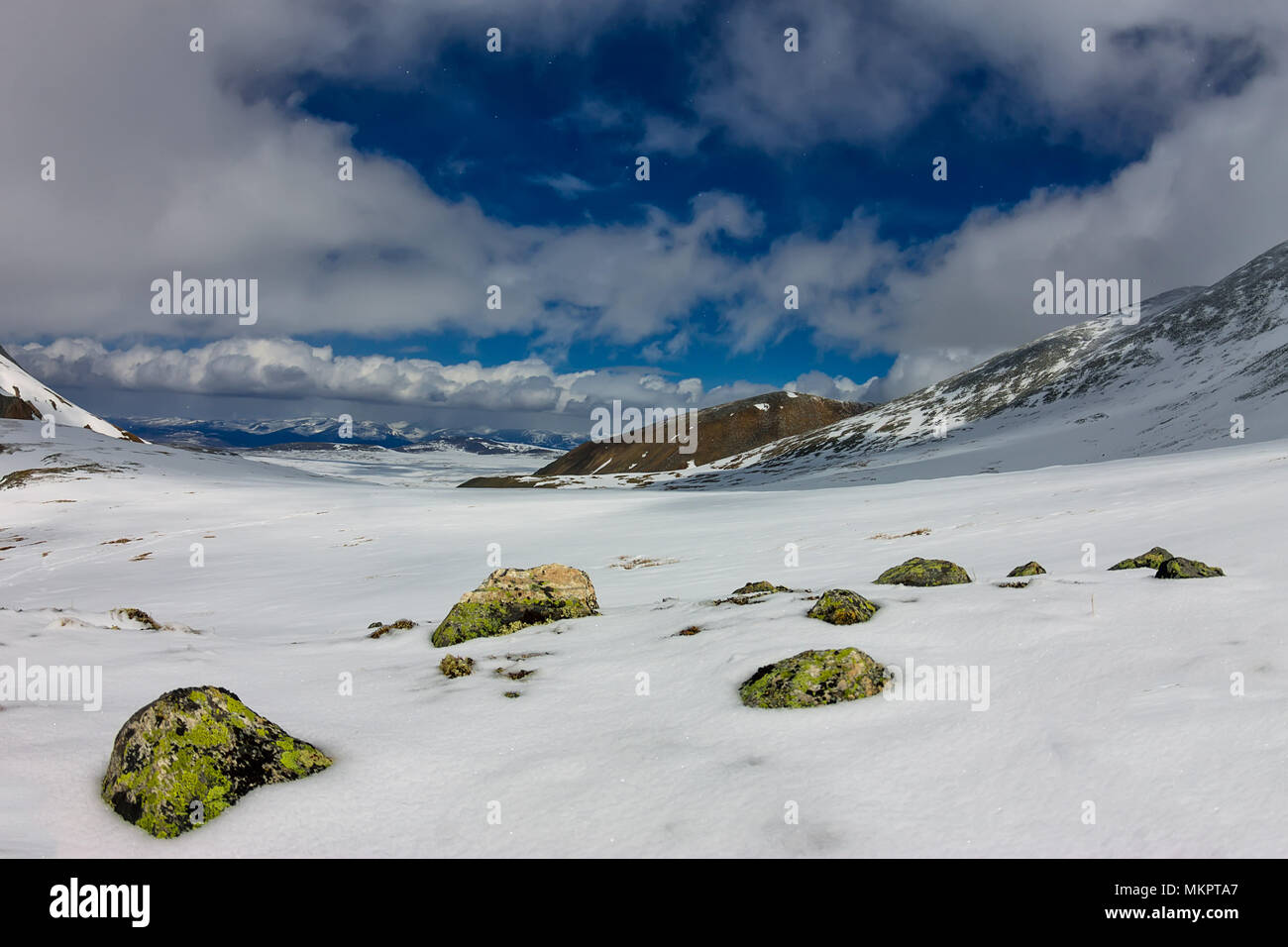 Snowy mountains aero photo drone, clouds approaching peaks and valley. - Stock Image