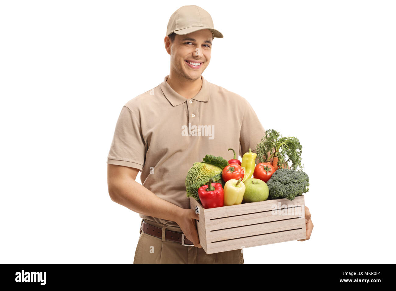 Delivery man holding a crate filled with groceries isolated on white background - Stock Image