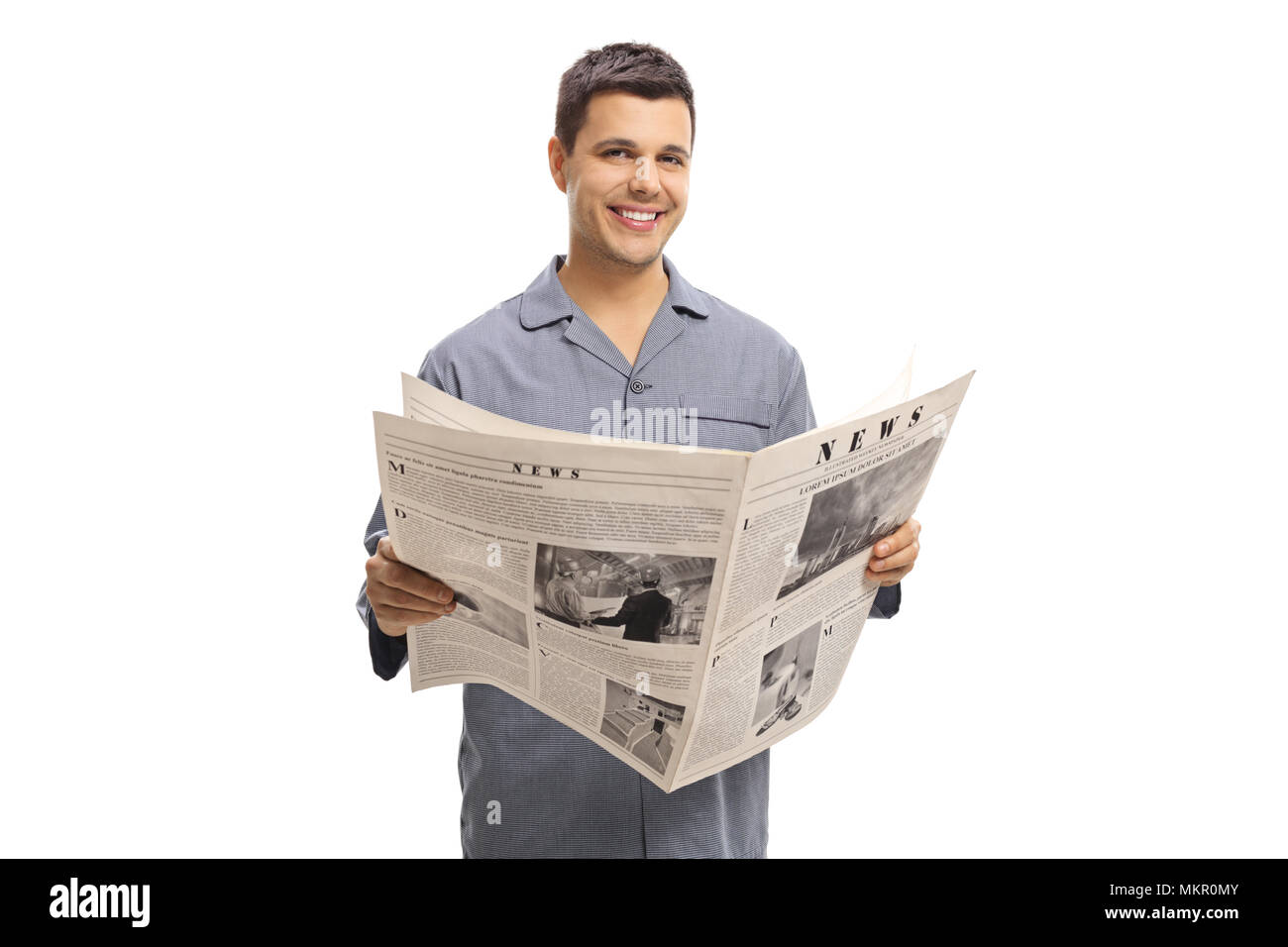 Young man in pajamas holding a newspaper isolated on white background - Stock Image