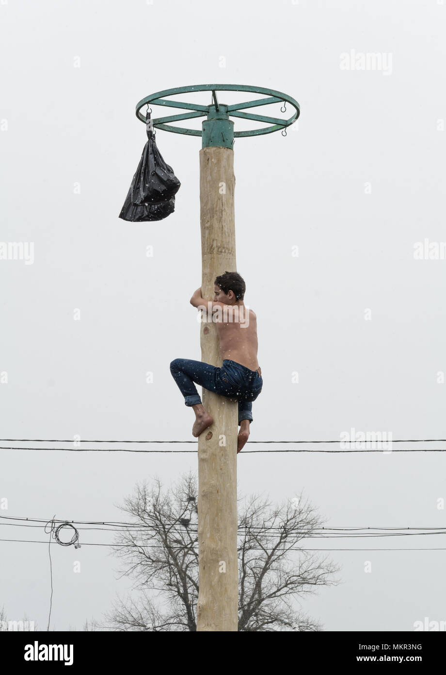 TIRASPOL, MOLDOVA-FEBRUARY 18, 2018: Boy climbing on a wooden pole for the prize. Slavonic folk pagan holiday Maslenitsa (Shrovetide) - a symbolic mee Stock Photo