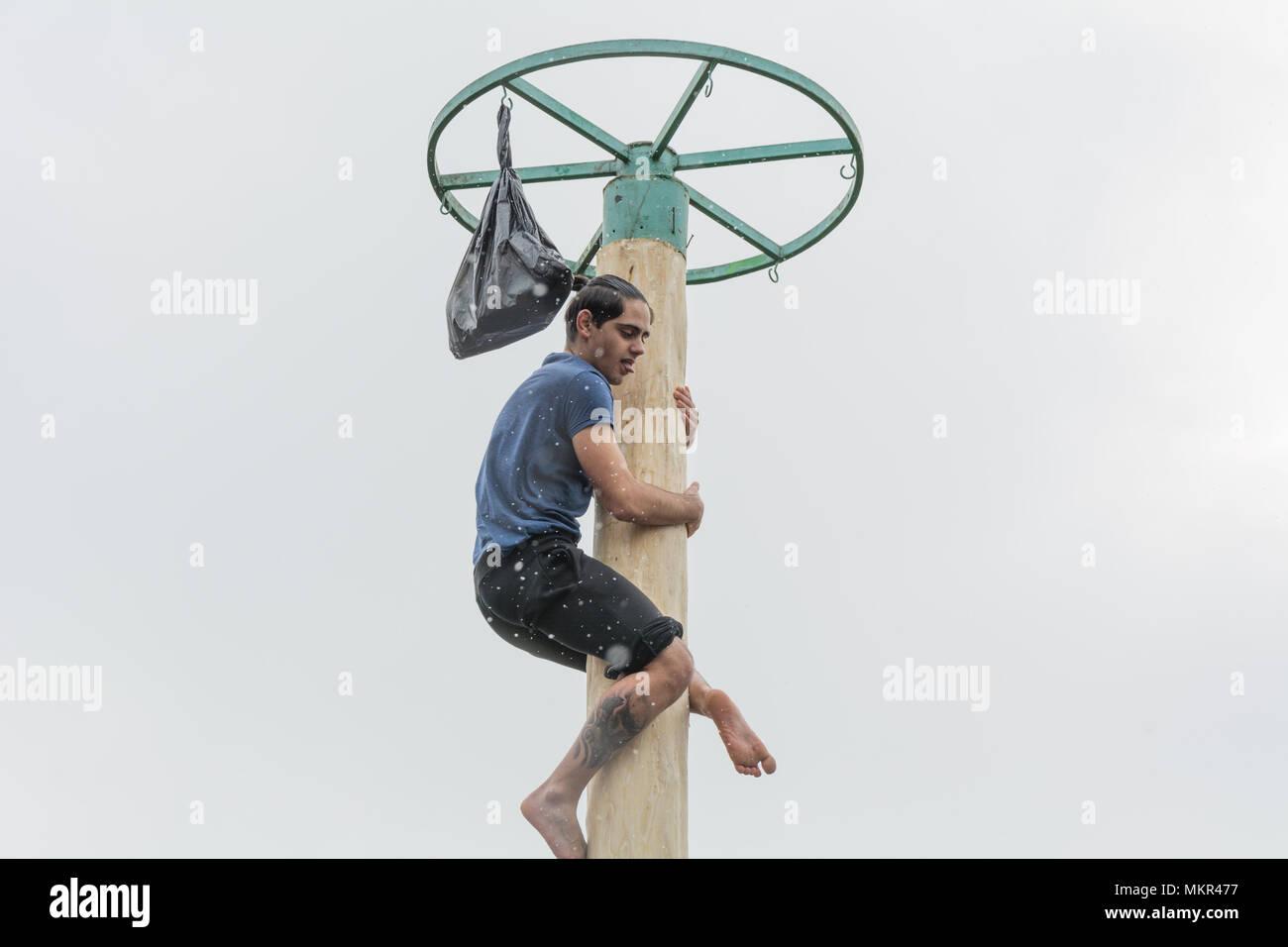 TIRASPOL, MOLDOVA - FEBRUARY 18, 2018: Young man climbing on a wooden pole for the prize. Slavonic folk pagan holiday Maslenitsa (Shrovetide) - a symb - Stock Image