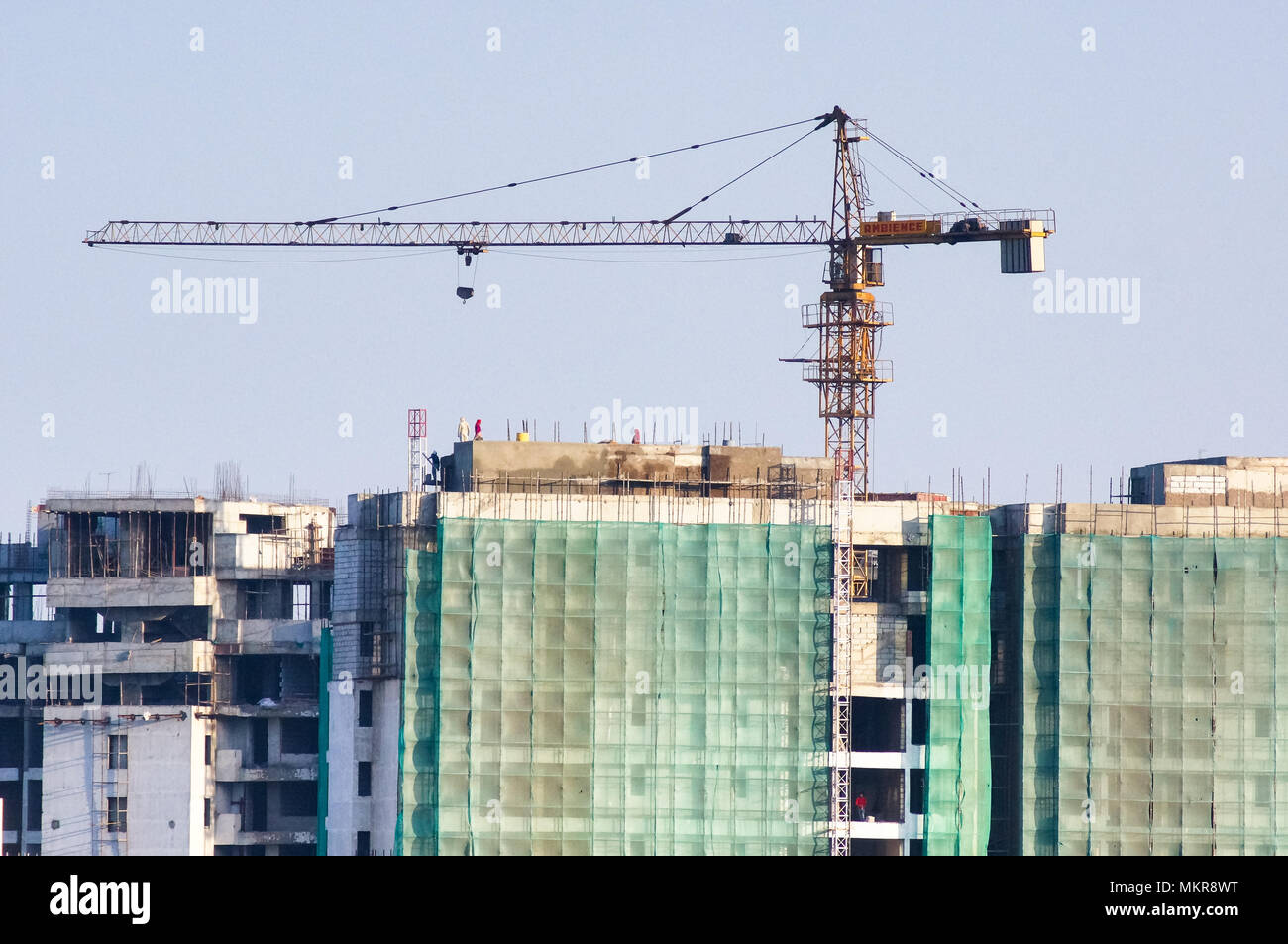 Under construction building with the concrete structure exposed and covered with green safety nets. The construction crane on top is an essential for building these high rise sky scrapers in delhi, jaipur, noida, gurgaon , lucknow, bangalore, hyderabad and other indian cities - Stock Image