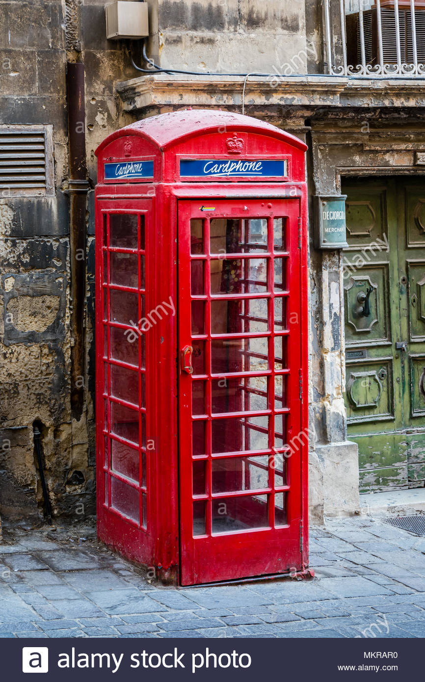 British old red telephone box relocated to a street in Valletta Malta where calls can still me made - Stock Image