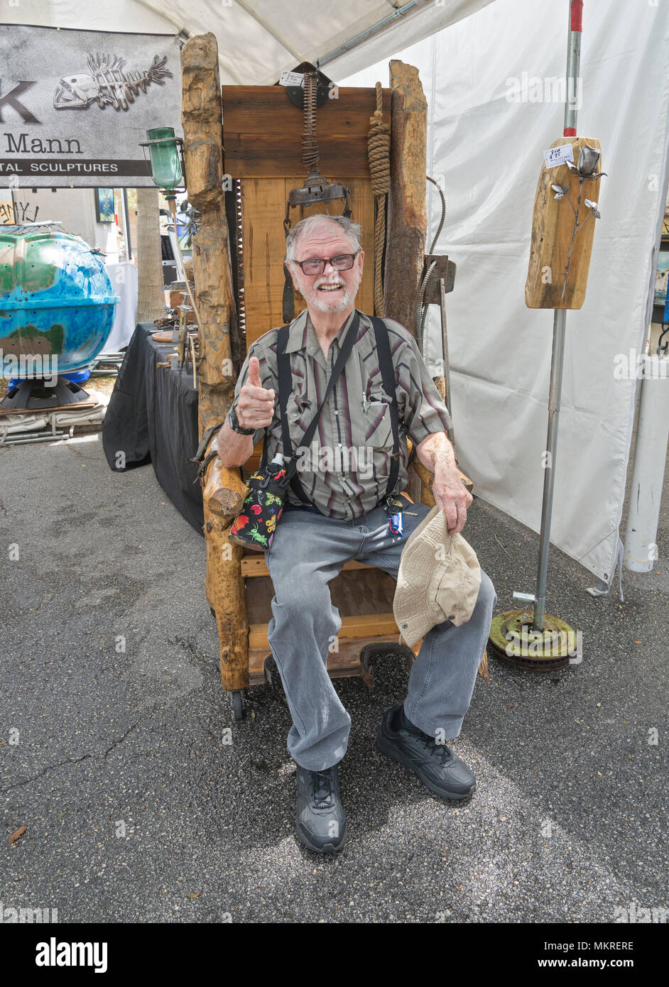Spring Festival in Gainesville Florida features a variety of expression and experiences. Man tries out a Wooden Electric Chair creation for sale. & Spring Festival in Gainesville Florida features a variety of ...